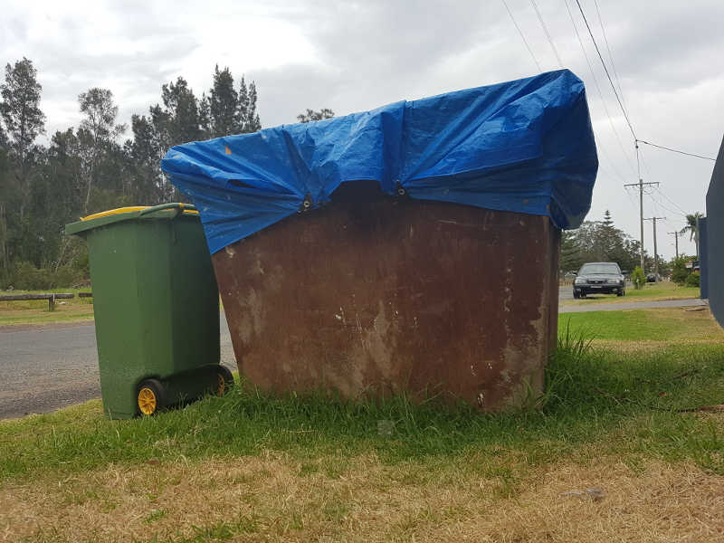 Keep others out of your skip bin by tying a tarp over it.